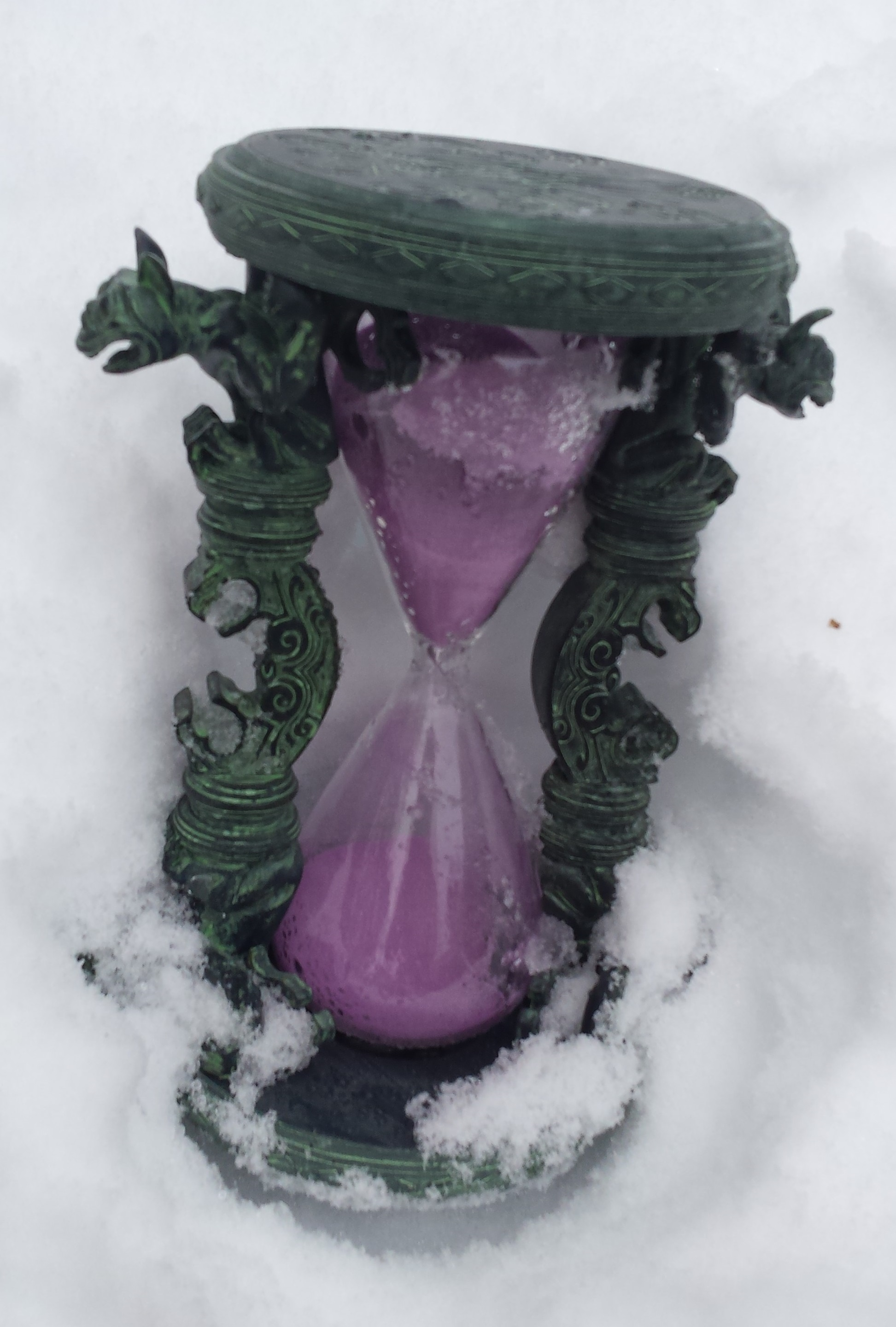 An hourglass filled with purple sand, rests in the snow