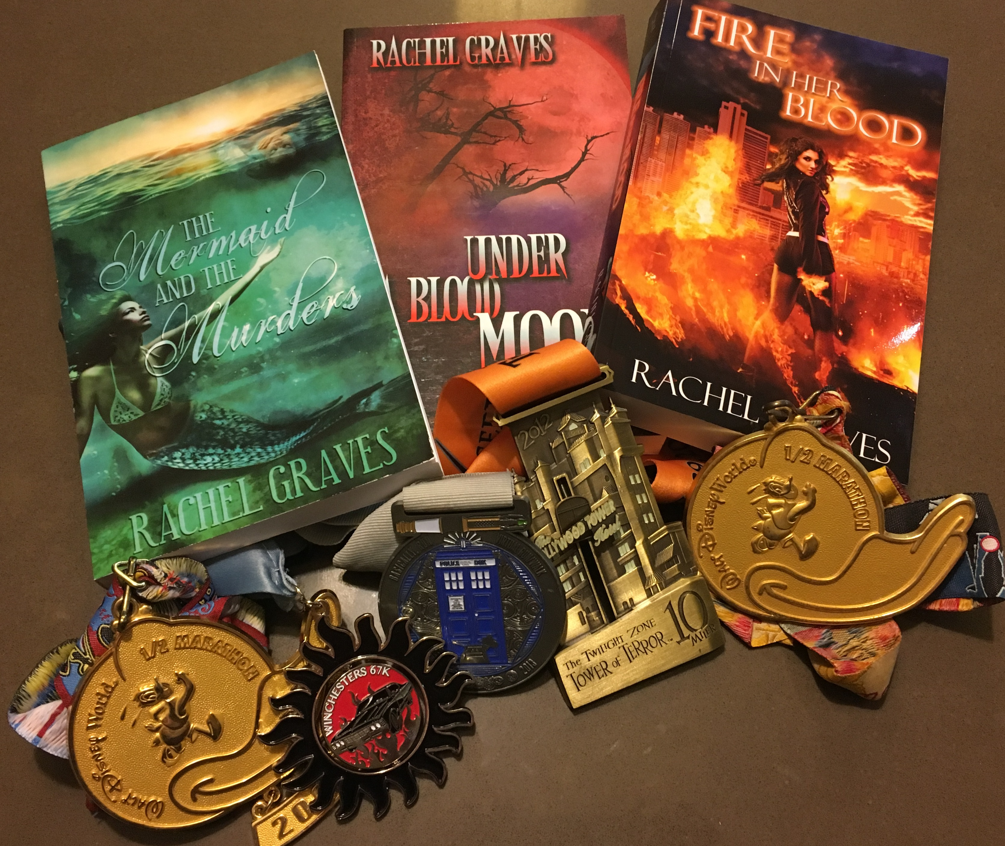 A stack of my published novels and several medals from races I've finished